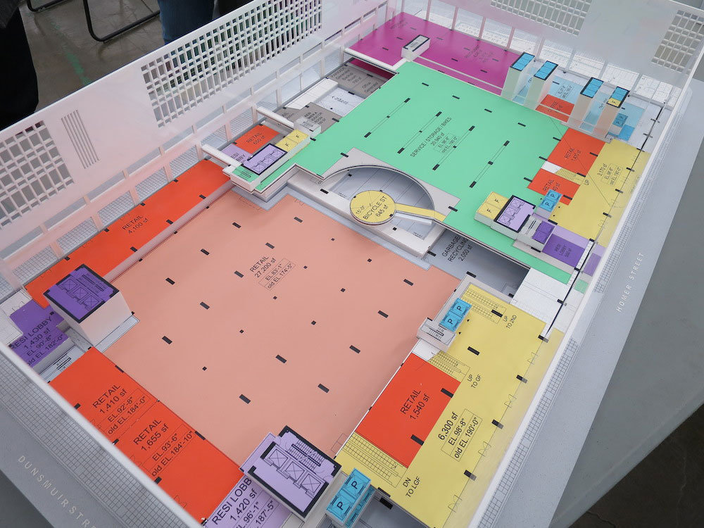 Diagram model of the second floor with retail (light red and orange), retail concourse (yellow), bike storage (turquoise), restaurants (fuschia), and the office lobby and accesses (blue).!